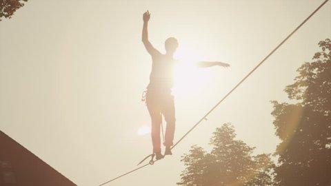 SLOW MOTION: Young man walking on slackline at golden sunset