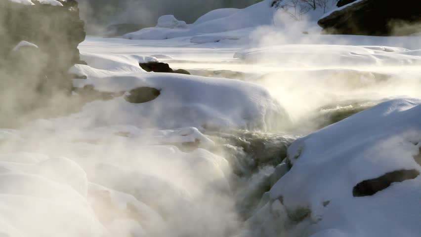 Cold winter sunrise, twenty below zero cold air and sunlight cause smoke like mist on ridge of waterfall