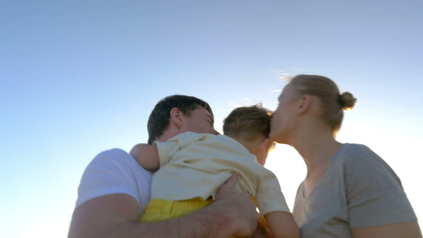 Steadicam slow motion shot of a boy running to his parents. They take him in arms, hug and kiss him.