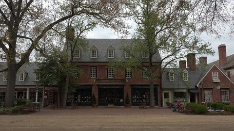 WILLIAMSBURG, VIRGINIA - APR 2015: Colonial Williamsburg Virginia main street tourist shops 4K. Living history museum and city district. Colonial America before and during American Revolutionary War