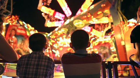 Two young brothers next to their mother admiring the spinning carousel at night, at amusement park in France - slow motion