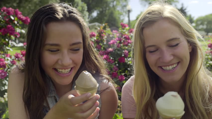 Closeup Of Best Friends Eating Ice Cream Cones They Smile And Hug