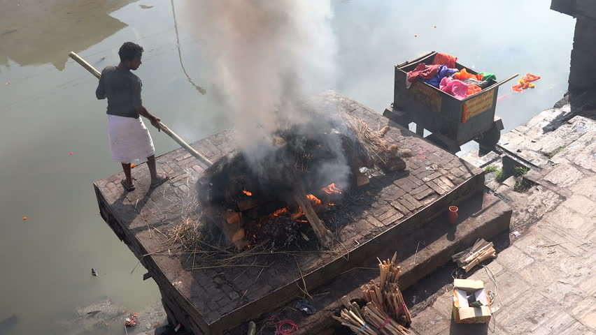 KATHMANDU, NEPAL - 5 JANUARY 2015: A caretaker burns the remains of a deceased person at the burning ghats inside the Hindu Pashupatinath temple complex in Kathmandu.