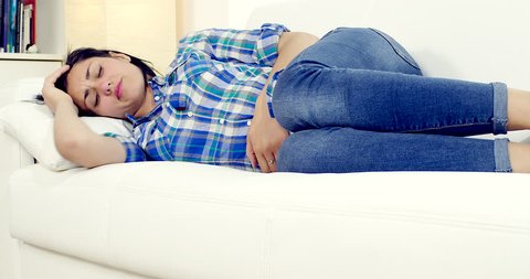 Beautiful woman with strong stomach ache menstruation problem lying on sofa at home