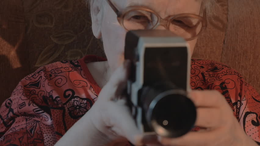 Slow motion, steadicam and close-up shot of an aged woman in glasses using retro video camera at home