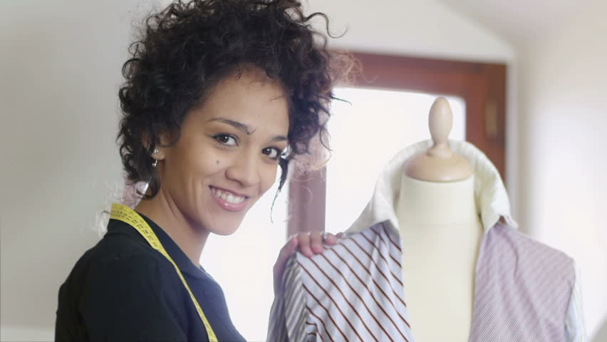 Young fashion designer, tailor and dressmaker adjusting clothes on tailoring mannequin and smiling at camera in studio