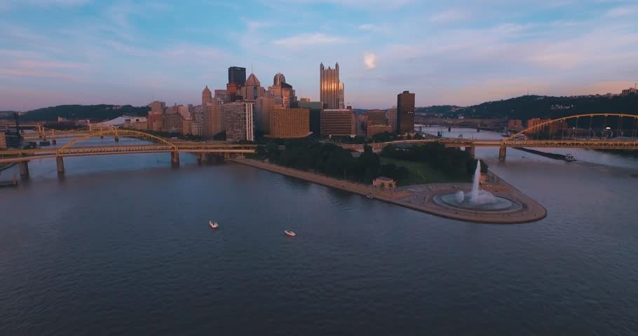 An aerial approach just off the top of the water towards Pittsburgh, Pennsylvania and Point State Park at sunset. (Pittsburgh PA, July 2015)