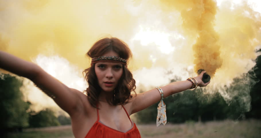 Beautful boho girl in a natural park playing and dancing with yellow smoke in Slow Motion