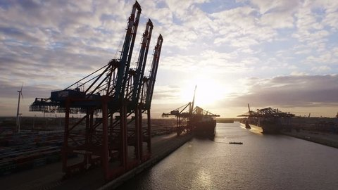 Flight over Hamburg container port with ships and cranes at sunset
