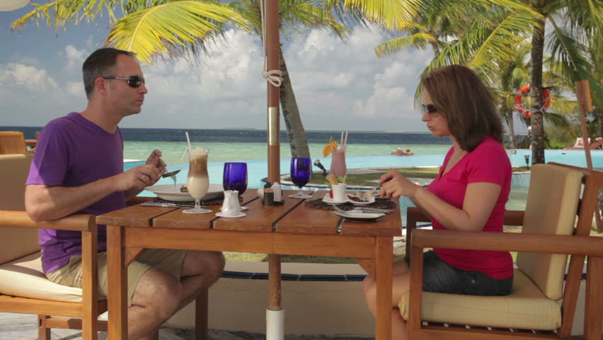 couple having lunch on a tropical beach terrace