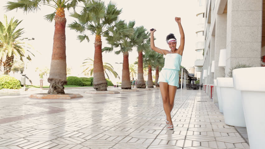 Beautiful african american teenager funky girl using technology headphones and smartphone to listen to music, dance and sing along while on holiday in a coastal palm trees boulevard, outdoors holiday. | Shutterstock HD Video #11060771