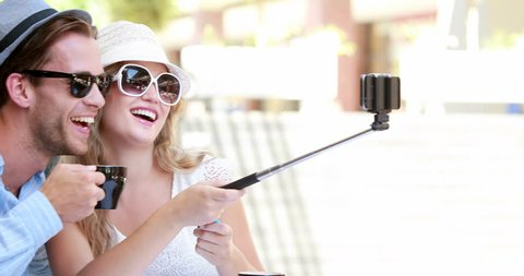Cute couple using a selfie stick in high quality 4k format