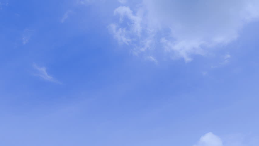 Beautiful white clouds soar across the screen in time lapse over a deep blue sky background. #11079131