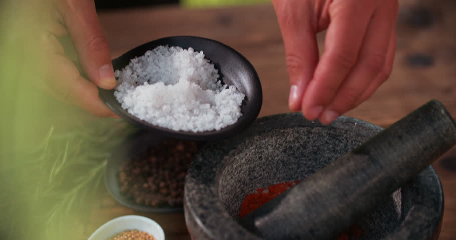 Hands adding a pinch of salt into a dark stone mortar and pestle to show how to make a delicious dry seasoning for meat with other spices and herbs around on the wooden table