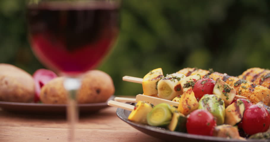 Vegetable kebabs, corn and asparagus grilled and looking delicious presented on a dark plate on a vintage wooden table