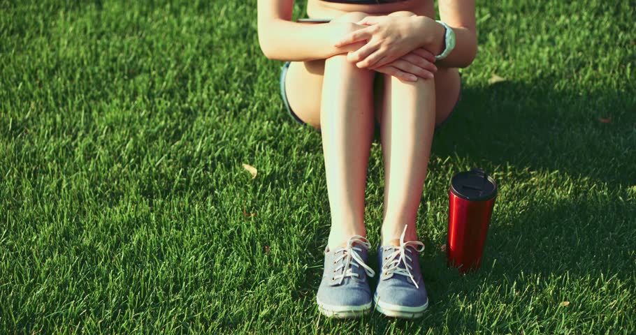 Female feet in sneakers gumshoes moving and posing on a sunlit green grass, close up. Woman in blue jeans color sports shoes sitting on the lawn with a thermal mug. Slow motion, 120fps. 4K, DCi. #11142584