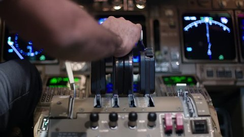 Detail shot of airline pilot's hand pushing forward on 747 jet throttle.  Rear view, originally recorded in 4K.
