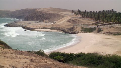 A pan from Salalah Port and Free Zone in Oman to a white beach and the dramatic mountainous coastline of the Indian Ocean