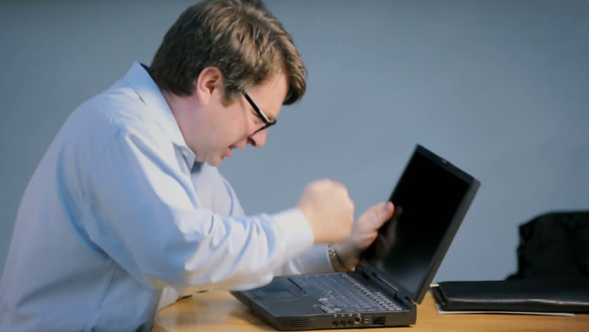 Stressed businessman smashing and breaking computer