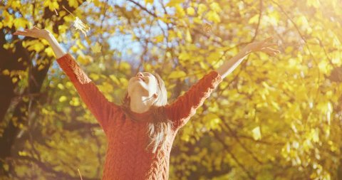 Happy woman throwing leaves in Autumn in slow motion, smiling. Slow Motion 120 fps. Joyful and excited young woman having fun throwing yellow leaves in the sunny fall park. 4k graded from RAW.