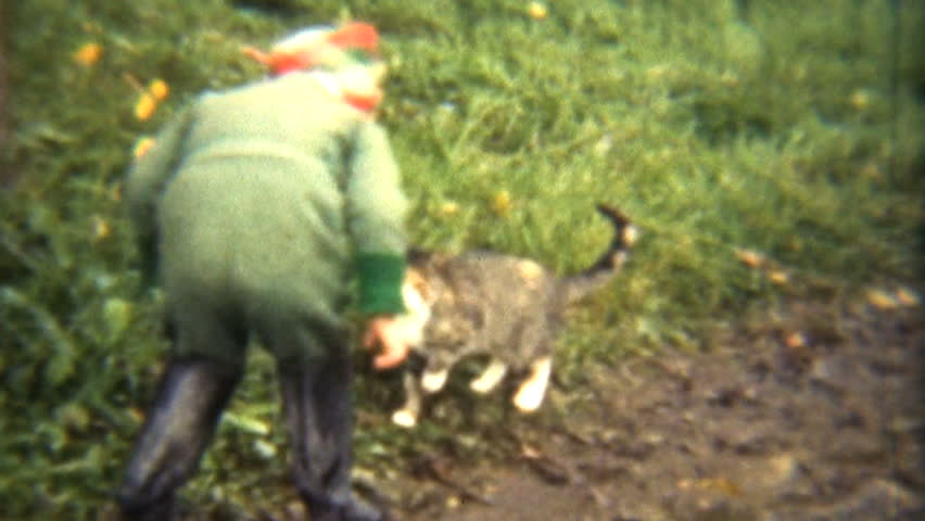 A cute little red headed girl plays with her cats and dogs while her father crouches nearby. from 8mm reels