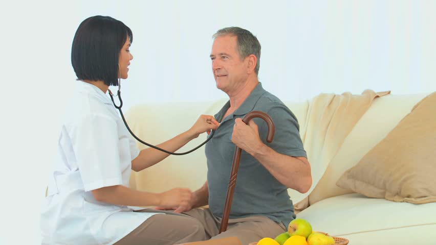 Asian nurse listening to heartbeat of an elderly man in the living room