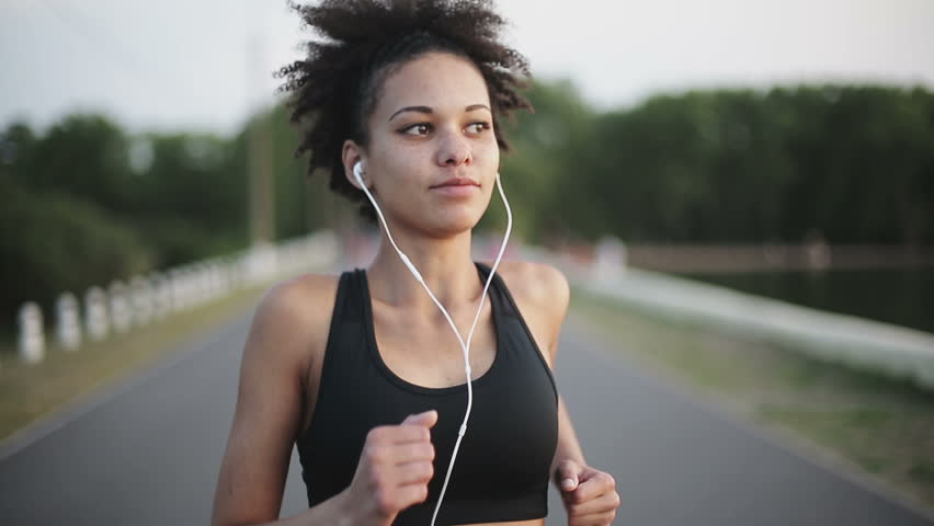 Woman running at sunrise listening to music with earphones #11201741