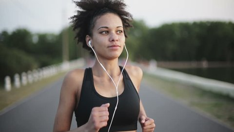 Woman running at sunrise listening to music with earphones