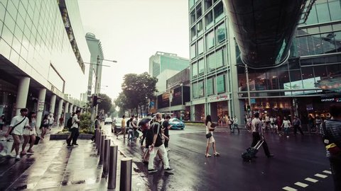 SINGAPORE CITY/SINGAPORE - JJULY 31, 2015: Timelapse Cars stop at traffic lights for pedestrians to cross Orchard Road. The road is a boulevard that is the retail and entertainment hub of Singapore.