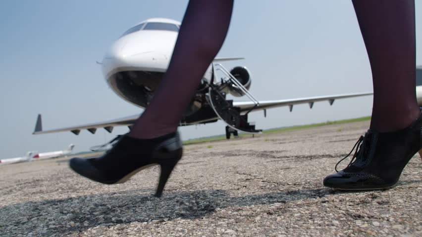 Detail of woman's feet wearing stockings and high heels as she walks right to left in front of a private jet.  Close view, originally recorded in slow motion 4K at 60fps.