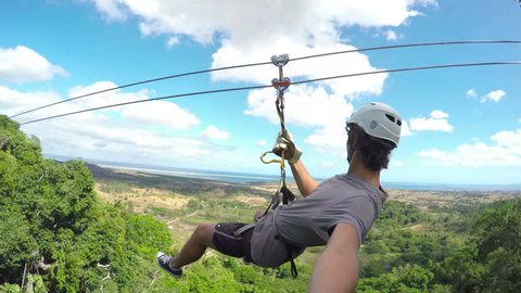 POV Young Happy Man Zip Lining In Tropical Jungle