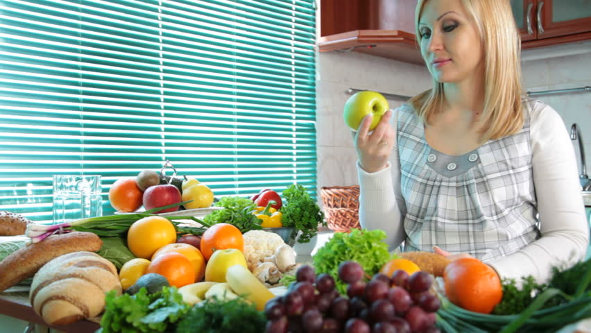 Pregnant woman eating apple near a lot of vegetables and fruits in the kitchen