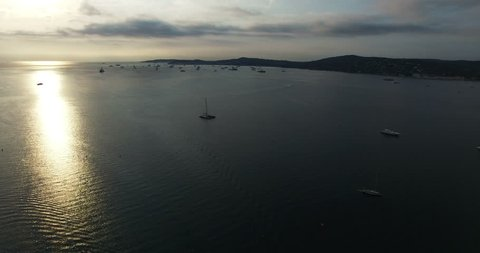 HQ Aerial Drone Video (Ultra HD) of the Bay of St. Tropez with big yachts waking up in the early morning sunset.
