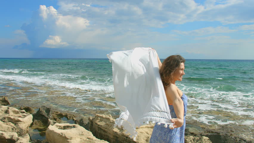 Young attractive woman holding white scarf in the wind on seashore, freedom | Shutterstock HD Video #11266361