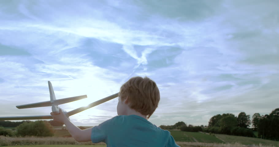 Boy playing outdoors with toy airplane at sunset time | Shutterstock HD Video #11309267