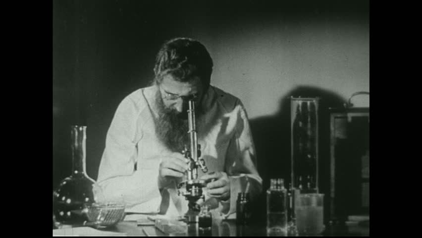 UNITED STATES 1940s. Scientist in laboratory looks into microscope. Two scientists work in lab.