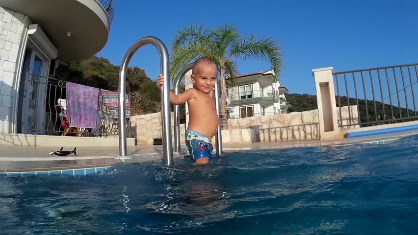 Bald toddler stands and plays on the ladder to the swimming pool as viewed from the water side