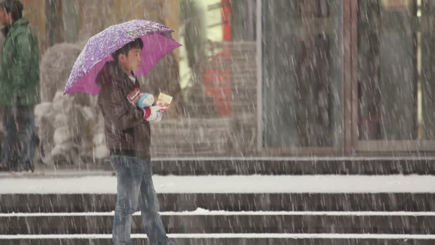 Shenyang, China - December 2010: A Chinese boy waiting on the street with an umbrella as heavy snow falls in Shenyang, Liaoning Province, China.   Shutterstock HD Video #11336741