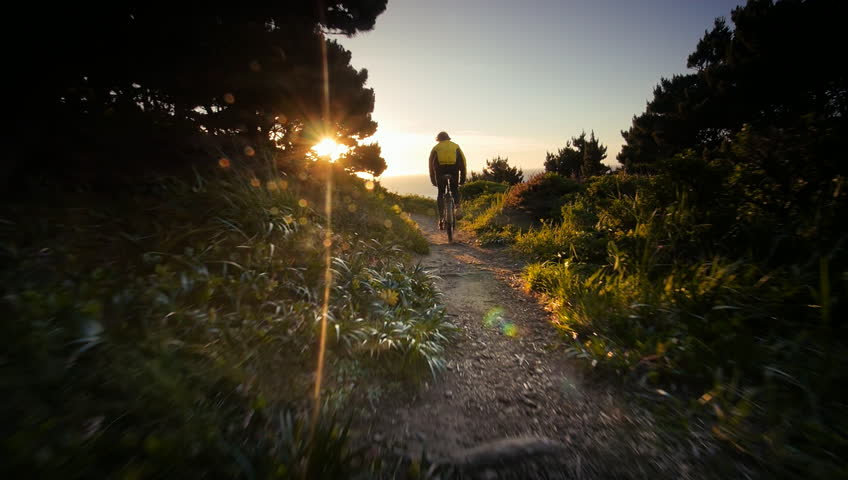 Man riding mountain bike on trail overlooking Pacific Ocean, Oregon
