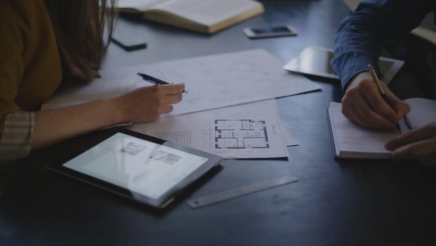 Video customer and the executor of the order for the construction sit opposite each other and discuss the subject of the order, are actively working with papers, drawings. each has its own subject for