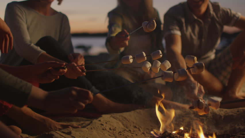 Group of People near Campfire Frying Marshmallows at Night. Shot on RED Cinema Camera in 4K (UHD).
