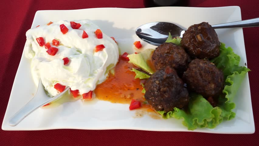 Albanian starters on the table covered with a red table-cloth at Kokomani winery close to Durres outside on a warm sunny day. Cheese plate with sauce, stuffed peppers and tomatoes, meatballs