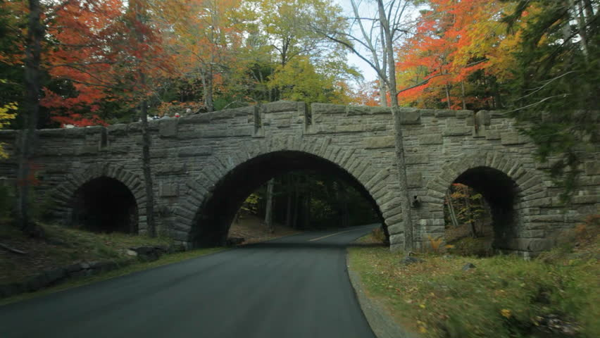 Driving on Stanley Brook Road passing under Stanley Brook Bridge with a horse-drawn carriage crossing on it, in Acadia National Park in Autumn.