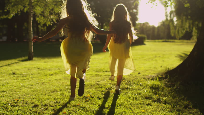 Two Girls are Running Away in Sunlight at Park. Shot on RED Cinema Camera in 4K (UHD).