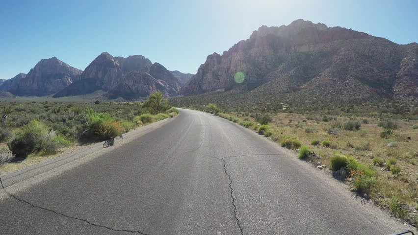 Viewpoint of a motorcyclist riding in Nevada Red Rock Canyon in 4K format. A biker rides down a scenic and empty road toward the mountains. | Shutterstock HD Video #11411204