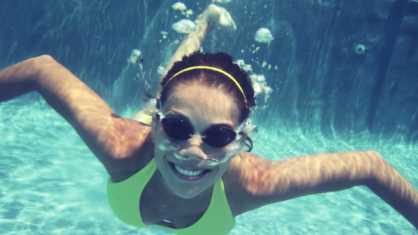 Video of young woman swimming in pool. Beautiful woman is wearing goggles. She is gesturing thumbs up in swimming pool.