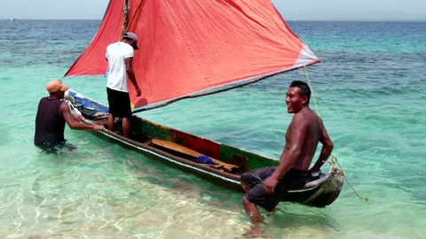 PANAMA, JUNE 2015 - Kuna Indians, native people, indigenous peoples, men fishing on sailing boat, fishermen on traditional dugout canoe with sail. Isla Aguja, archipelago of San Blas islands, Panama