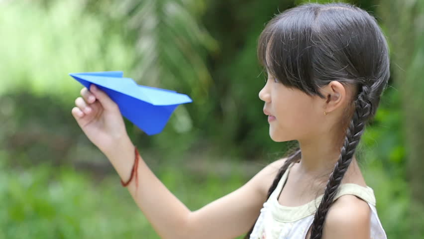 Slow motion of little Asian child playing with paper airplane in the park | Shutterstock HD Video #11468561