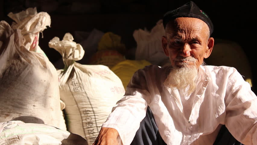 Xinjiang, China - October 2010: Close-up of an old Uighur man with a long beard and wearing muslim cap, sitting in front of sacks of grain in Tuyoq, Xinjiang Province, China.