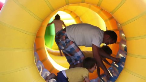 Father and two sons, having fun in a big rolling spherical ring, zorbing